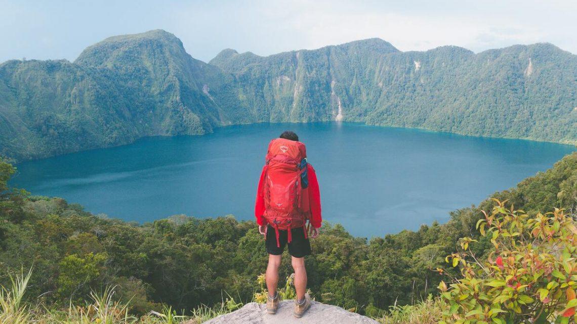 Randonneur solo devant lac avec sac rando rouge Osprey