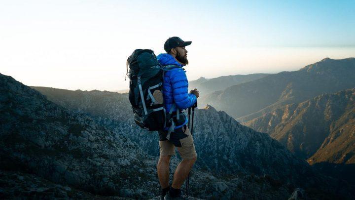 Homme porte sac de randonnée et bâtons de rando